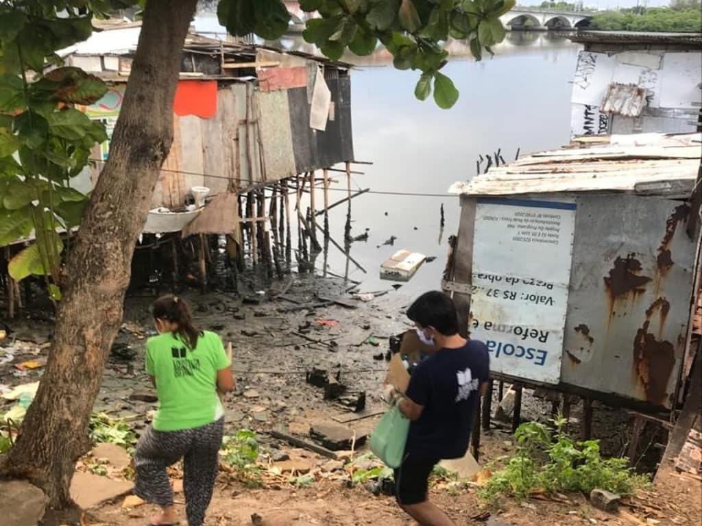 Entrega de alimentos na comunidade de palafitas ao lado da ponte do Pina